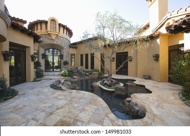 Paved courtyard garden with pond in house against clear sky