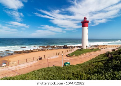 Paved Green vegetation and patterned walkway with metal barrier against red and white lighthouse against blue cloudy coastal seascape at Umhlanga, Durban, South Africa