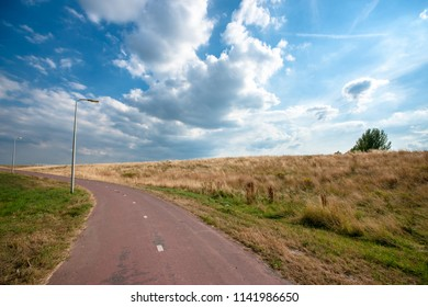 Paved hard stone road along dutch cultivated landscape. Blue skies, cumulus clouds, grassland and dikes