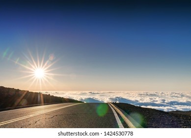 Paved highway above in high elevation, above clouds, with sun burst effect