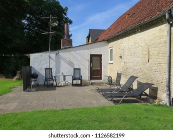 Paved patio area with seating at farm in Southern Denmark