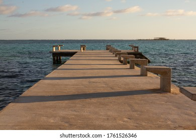Paved pier entering the sea with calm water on a sunny day and a platform built in the middle of the sea in the background