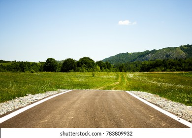 Paved road ending abruptly in the middle of a green plain with some trails ahead