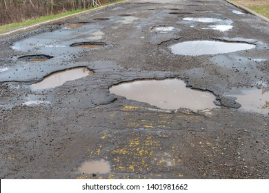 A paved road filled with many large potholes, the potholes are filled with water.