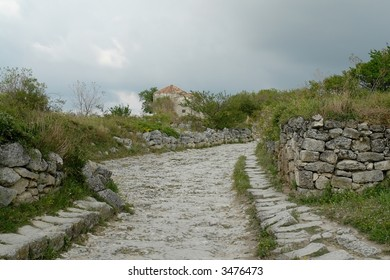 Paved road in the mountains with cloud sky at background