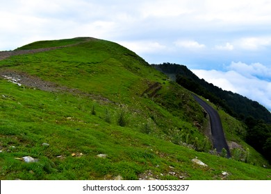 Paved road on green lush  hill top