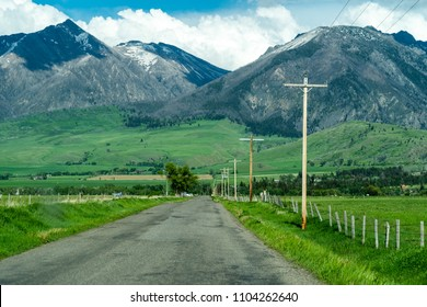Paved road with power lines leading into the Absaroka Mountain Range in Montana's Paradise Valley, located in Park County, Montana, on a partly cloudy spring day