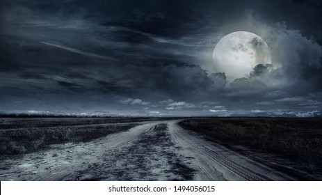 paved road through a field of wheat at night. Storm