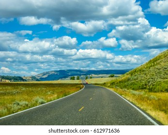 Paved road in the Yellowstone National Park, Wyoming, United States, between prairies, mountains and cloudy sky.
