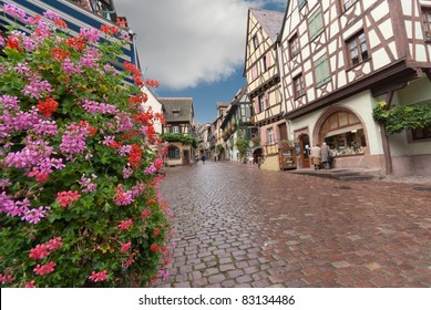 Paved street in Alsace with half-timbered houses and flowers