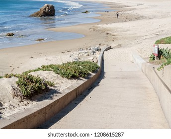 Paved walkway down to the beach. Sand and blue ocean in background.