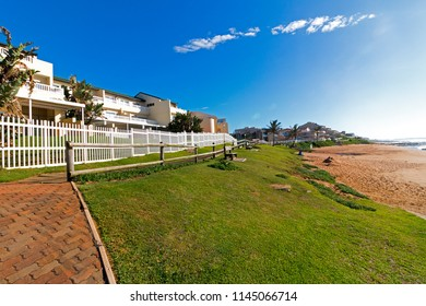 Paved walkway green lawn beach and ocean against comercial and residential buildings and blue cloudy sky landscape in Ballito, Durban, South Africa