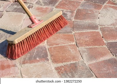 Paved walkway is grouted with fine-grained sand and a broom