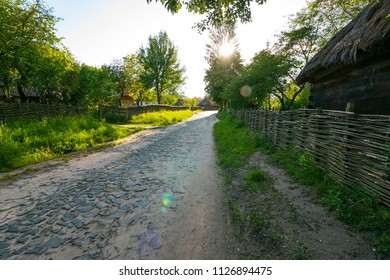 The pavement is laid out on old street with a wicker tin around wooden houses. Uzhhorod Ukraine