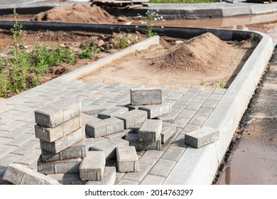Pavement repair and laying of paving slabs on the walkway, stacked tile cubes on the background. Laying paving slabs in the pedestrian zone of the city, sand filling. Road tiles and curbs