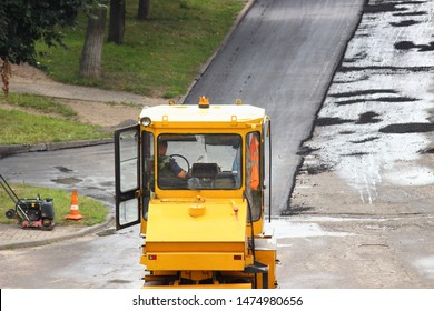 Pavement of the road, steamroller laying new asphalt in city Park, industrial machinery - close up cabin of yellow asphalt roller on summer day