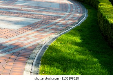 Pavement tile with drainage and shorn grass in landscape design