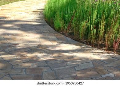 Gehweg aus gepflegtem Kalkstein In Gartenlandschaft. Hinterhofgarten Schattierter Fußweg von geteerten Steinplatten. Fahreibender Spaziergang im Garten. Schattiger Weg von Steinsteinen im Park.