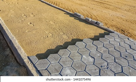 Pavement under construction. Cobblestone blocks and sands laid for installation of new sidewalk.