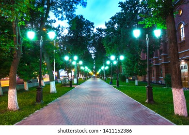 Pavement walkway at night in the green light of symmetrically lampposts, leading to the center of the frame. Pushkin street near the Opera and Ballet Theater, Ufa, Bashkortostan, Russia.