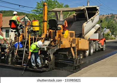 A paver finisher, asphalt finisher or paving machine placing a layer of asphalt during a repaving construction project