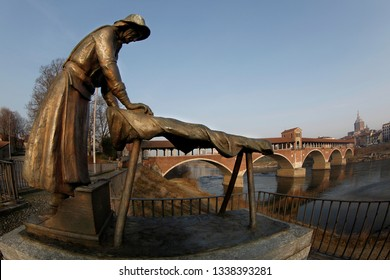 Pavia, Italy -10-02-2019:The washerwoman of the old village with the background of the Covered Bridge and the Cathedral