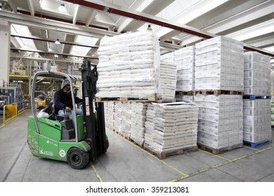 PAVIA, ITALY - 16 APRIL 2012: An employee using a forklift truck to maneuver a pallet load of bagged rice inside the warehouse at a rice processing and packaging plant in Pavia, Italy.