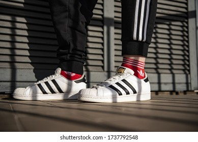 Pavia, Italy - January 30, 2020: Young man wearing Adidas Superstar on the balcony - illustrative editorial