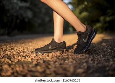 Pavia, Italy - July 8, 2018: Man wearing a pair of Nike Air Max Performance and walking on leaves