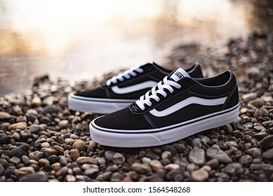 Pavia, Italy - November 6, 2019: Pair of Vans Old Skool shoes on a stones beach near the river - illustrative editorial