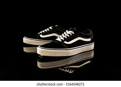 Pavia; Italy - November 9; 2019: Brand new black and white Vans Old Skool shoes; studio portrait on black background with reflection - illustrative editorial