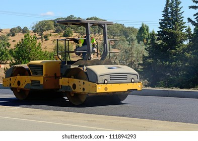 A paving crew  putting down a layer of asphalt on a new highway intersection project