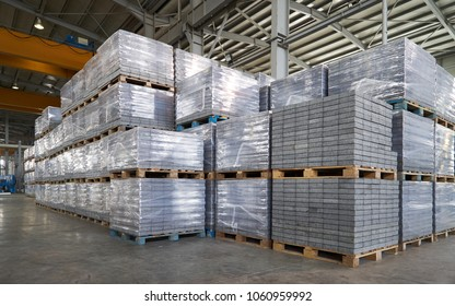 Paving slabs factory. Tiles piled in pallets. Warehouse paving slabs in the factory for its production