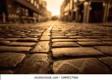 Paving stone and sunlight. Old street floor pavement background. Street tiles in europe and people walking. Cobbles at sunset. Sunlight on Cobbled Stones against european houses.