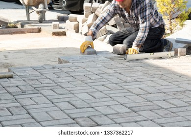 Paving stone worker is putting down paver blocks and pouring sand during a construction of a city street.