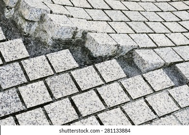 paving stones broken and cracked on pavement