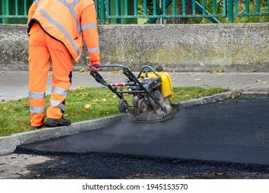 Paving worker uses vibratory plate compactor to compact new asphalt near curbstones