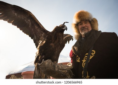 Pavlodar, Kazakhstan - March 22, 2015: An eagle hunter dressed in the traditional asian clothes holding a bird of prey during Nauryz (New Year) celebration according to the Eastern Calendar.