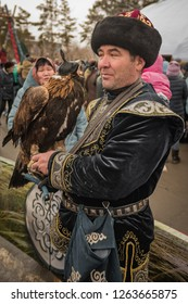 Pavlodar, Kazakhstan - March 22, 2018: An eagle hunter dressed in decorated traditional asian clothes, holding a bird of prey, celebration of Nauryz (New Year) according to the Eastern Calendar.