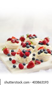 Pavlova berry cake with blueberries, strawberries, raspberries and vanilla ice cream on a marble background