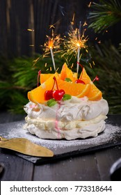 Pavlova cake with oranges and cocktail cherries on a dark background. Decorated with sparklers. Christmas, New Year theme.
