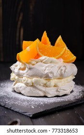 Pavlova cake with oranges on a dark background