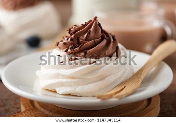Pavlova meringue cake with chocolate cream on brown background .