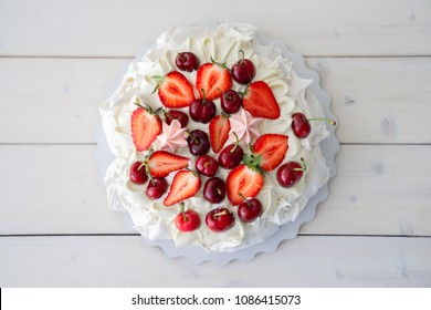 Pavlova Meringue dessert on light wooden table, top view. This is dessert made of round merengue and strawberry on top. White cake with berries