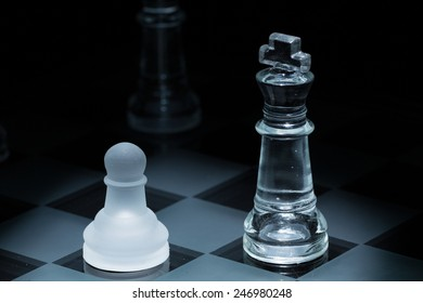 pawn and king in black background and center illumination