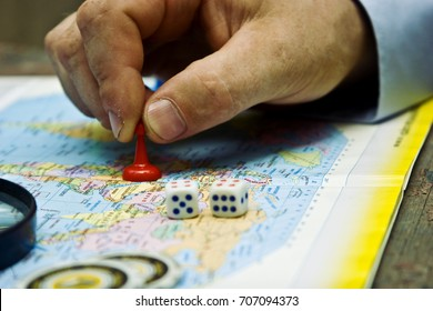 A pawn in a man's hand on a geographical map of the world against a background of a magnifying glass
