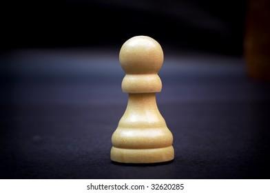 Pawn, wooden chess piece on dark background.