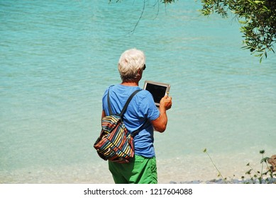PAXOS, GREECE - JUNE 11, 2014: A man uses a tablet to photograph the sea at Harami beach in Lakka on the Greek island of Paxos. Popular with tourists, the small island has a population of around 2300.