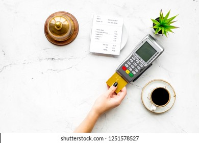 Pay the bill by payment terminal. Woman's hand insert bank card in payment terminal near bill, service bell, coffee on white stone background top view copy space