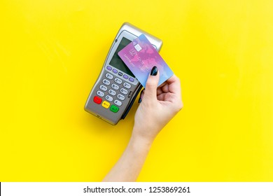 Pay by payment terminal. Paypass  technology. Woman's hand hold credit card, bring card to terminal  on yellow background top view copy space